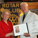 Mike Hardy receives congratulations on his Mercer Munn award from Rotary Club President Sue Moore.